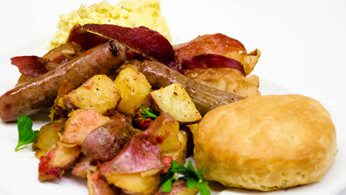 Full breakfast with scrambled eggs, bacon or sausage, and home fried potatoes